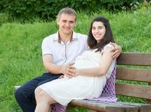 Les couples heureux dans la ville d'été garent la femme extérieure et enceinte, le jour ensoleillé lumineux et l'herbe verte, bea Image stock