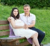 Les couples heureux dans la ville d'été garent la femme extérieure et enceinte, le jour ensoleillé lumineux et l'herbe verte, bea Photos libres de droits