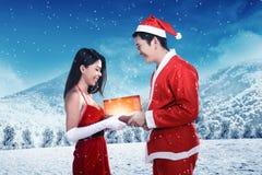 Les couples heureux dans le costume du père noël célèbrent Noël Photographie stock