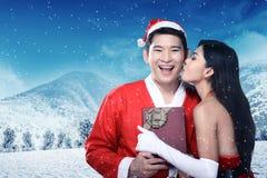 Les couples heureux dans le costume du père noël célèbrent Noël Photos stock