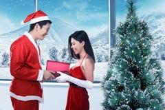 Les couples heureux dans le costume du père noël célèbrent Noël Photos libres de droits