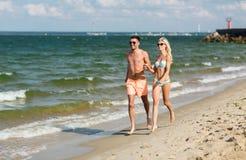 Les couples heureux dans les vêtements de bain fonctionnant l'été échouent Photos libres de droits