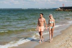 Les couples heureux dans les vêtements de bain marchant l'été échouent Photo stock