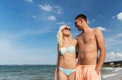 Les couples heureux dans les vêtements de bain marchant l'été échouent Photographie stock libre de droits
