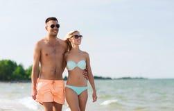 Les couples heureux dans les vêtements de bain marchant l'été échouent Image stock