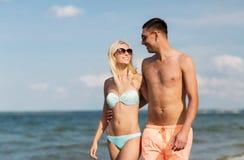 Les couples heureux dans les vêtements de bain marchant l'été échouent Photographie stock