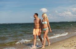 Les couples heureux dans les vêtements de bain marchant l'été échouent Photos stock