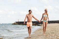 Les couples heureux dans les vêtements de bain marchant l'été échouent Image libre de droits