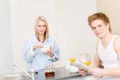 Les couples heureux de déjeuner mangent le journal affiché par céréale Photos stock