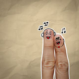 Les couples heureux de doigt dans l'amour avec le smiley peint et chantent un s Photo libre de droits