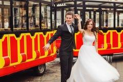 Les couples heureux de mariage dansent derrière un autobus de touristes Photographie stock