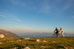 Les couples heureux de mountainbike dehors ont l'amusement ensemble sur un coucher du soleil d'après-midi d'été photos stock
