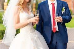 Les couples heureux de nouveaux mariés boivent du vin blanc de champagne de mariage Les mains des jeunes mariés avec les anneaux  Image stock