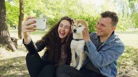 Les couples heureux de propriétaires fiers de chien prennent le selfie avec le bel animal familier ayant l'amusement et l'embêtan banque de vidéos