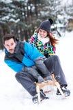 Les couples heureux de sourire apprécient dans sledding au jour d'hiver de neige Photo stock