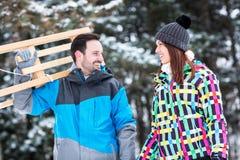 Les couples heureux de sourire apprécient dans sledding au jour d'hiver de neige Image stock