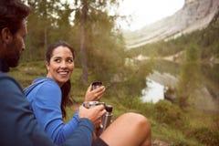 Les couples heureux de sourire d'homme et de femme apprécient la vue de panorama de lac avec la lumière de fusée du soleil Groupe Photo stock