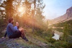 Les couples heureux de sourire d'homme et de femme apprécient la vue de panorama de lac avec la lumière de fusée du soleil Groupe Photos stock