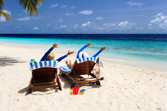 Les couples heureux détendent sur une plage tropicale Photos stock