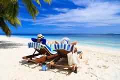 Les couples heureux détendent sur une plage tropicale Image libre de droits