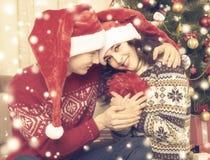 Les couples heureux embrassent près de l'arbre et de la décoration de Noël à la maison Vacances d'hiver et concept d'amour Jaune  Images libres de droits