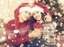 Les couples heureux embrassent près de l'arbre et de la décoration de Noël à la maison Vacances d'hiver et concept d'amour Jaune  Photographie stock libre de droits