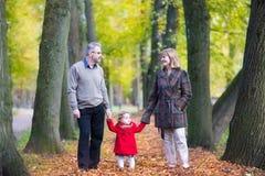 Les couples heureux en automne se garent avec la fille d'enfant en bas âge Photos stock