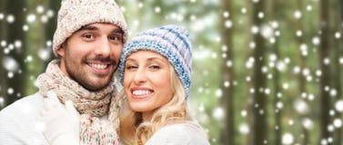 Les couples heureux en hiver portent au-dessus de la forêt et de la neige Images libres de droits