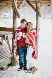 Les couples heureux enveloppés dans le plaid boivent du thé chaud dans une forêt neigeuse Photos libres de droits