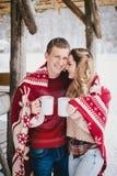 Les couples heureux enveloppés dans le plaid boivent du thé chaud dans une forêt neigeuse Image stock