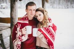 Les couples heureux enveloppés dans le plaid boivent du thé chaud dans une forêt neigeuse Photographie stock
