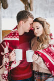 Les couples heureux enveloppés dans le plaid boivent du thé chaud dans une forêt neigeuse Photo stock