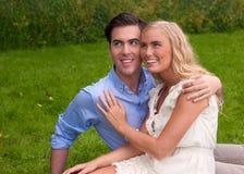 Les couples heureux et beaux emracing à l'été pique-niquent Photos stock