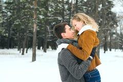Les couples heureux extérieurs dans l'amour posant en hiver froid survivent Photographie stock libre de droits