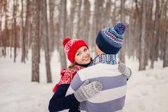 Les couples heureux extérieurs dans l'amour posant en hiver froid survivent Jeune garçon et fille ayant l'amusement extérieur Image libre de droits