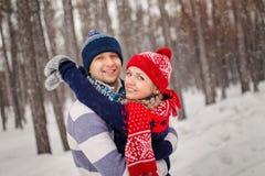 Les couples heureux extérieurs dans l'amour posant en hiver froid survivent Jeune garçon et fille ayant l'amusement extérieur Photographie stock