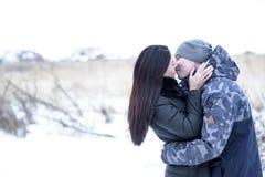 Les couples heureux extérieurs dans l'amour posant l'hiver froid survivent Photo stock