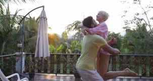 Les couples heureux marchant à l'embrassement de rotation de terrasse au coucher du soleil dehors mélangent l'homme et la femme d banque de vidéos