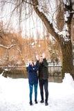 Les couples heureux ont l'amusement dans le parc d'hiver photo stock
