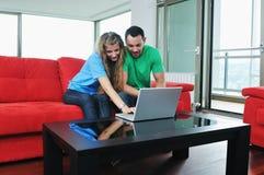 Les couples heureux ont l'amusement et le travail sur l'ordinateur portatif à la maison Images stock