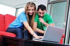 Les couples heureux ont l'amusement et le travail sur l'ordinateur portatif à la maison Photographie stock libre de droits