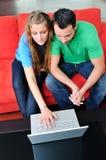 Les couples heureux ont l'amusement et le travail sur l'ordinateur portatif à la maison Photo libre de droits