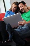 Les couples heureux ont l'amusement et le travail sur l'ordinateur portatif à la maison Image libre de droits