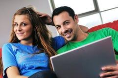 Les couples heureux ont l'amusement et le travail sur l'ordinateur portatif à la maison Photos stock