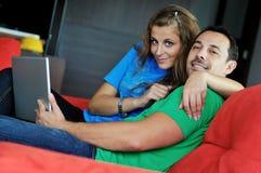 Les couples heureux ont l'amusement et le travail sur l'ordinateur portatif à la maison Images libres de droits