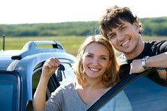 Les couples heureux s'approchent du véhicule neuf Images stock