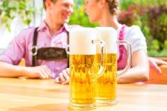 Couples heureux en bière potable de jardin de bière Photographie stock libre de droits