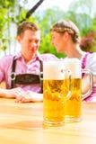 Couples heureux en bière potable de jardin de bière Images libres de droits