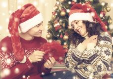 Les couples heureux se reposent près de l'arbre et de la décoration de Noël à la maison Vacances d'hiver et concept d'amour Jaune Photographie stock libre de droits