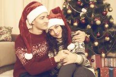 Les couples heureux se reposent près de l'arbre et de la décoration de Noël à la maison Vacances d'hiver et concept d'amour jaune Photographie stock
